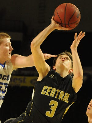 Central Magnet's Will Carver puts up a shot over the outstretched arm of Macon County's Heston King.