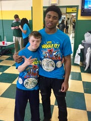 Hillsboro High School star running back Jacob Frazier, right, poses with his junior friend Stephen Mast after giving Mast a replica wrestling belt and T-shirt from Mast's favorite WWE tag team The New Day Wednesday in the school cafeteria.