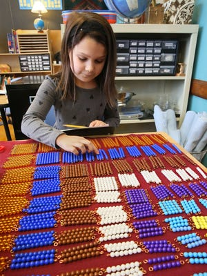 Isabella Martinez, 8, uses colored beads to visualize math concepts at Howard Avenue Montessori School in December. Isabella is a second-grade student in a combined first, second and third grade class.