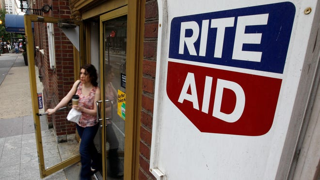FILE- In this June 20, 2011, file photo, a woman exits a Rite Aid store, in Philadelphia.