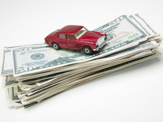 Miniature car on stack of money