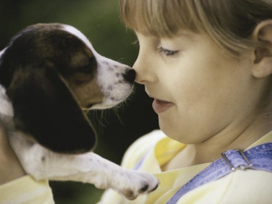 Close-up of a girl nuzzling her puppy
