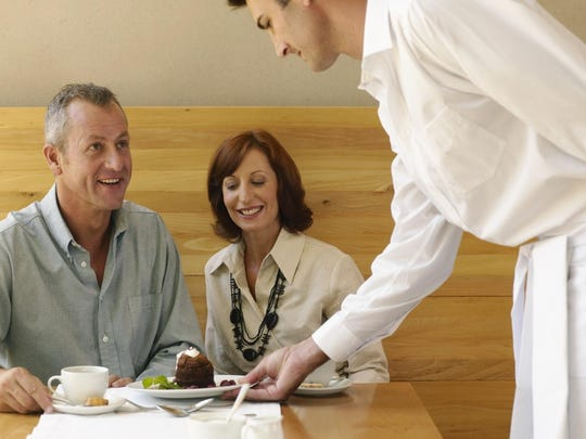 Waiter serving couple dessert, man smiling at waiter