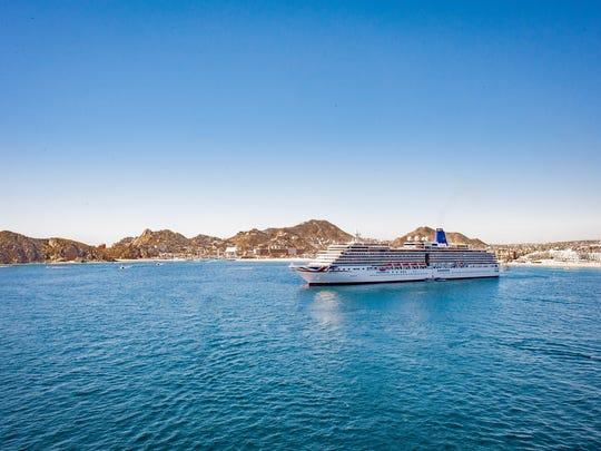 A cruise ship docked near an island port.