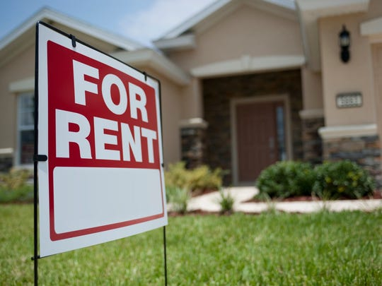 "A ""for rent"" sign in the front lawn of a house."