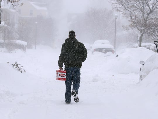Andrew Jones makes his way on to a snowbound Vassar Street in Rochester. in 2017  His car was snowed in so he decided to walk to a corner store.