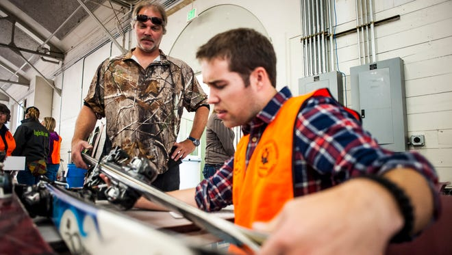 Paul Kinney, left, talks to Cody Brandt, right, as Brandt prices his skis during the Ski and Board Swap in Montana ExpoPark's Trades and Industry Building Friday. The Ski Club fundraiser features new and used equipment from the public as well as third parties such as Showdown Montana Ski Area.