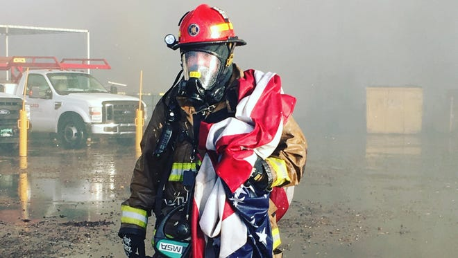 Capt. Nick Ells saves the United States' flag from a Phoenix fire that took over a recycling plant Tuesday, March 22, 2016.