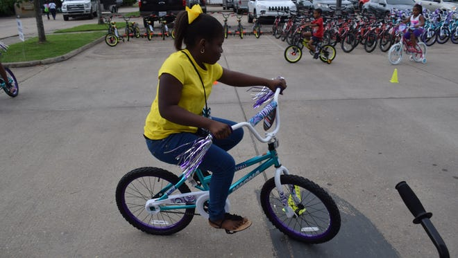 "E'Myia Hall rides her new bike around an obstacle course at Laborde Earles Law Firm in Marksville. The Laborde Earles Law Firm gave away 231 children's bikes and helmets to children in the Lafayette and Central Louisiana areas as part of their ""Bike It Forward"" program, which promotes community involvement, child safety, child health and well-being."