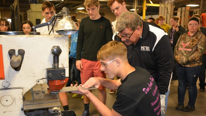 John Wilz, Hi Tec Fabrication operations manager, supervises Peyton Hurth, a sophmore student at Sevastopol High School, as he punches a hole through a piece of steel Friday, Oct. 20, 2017.