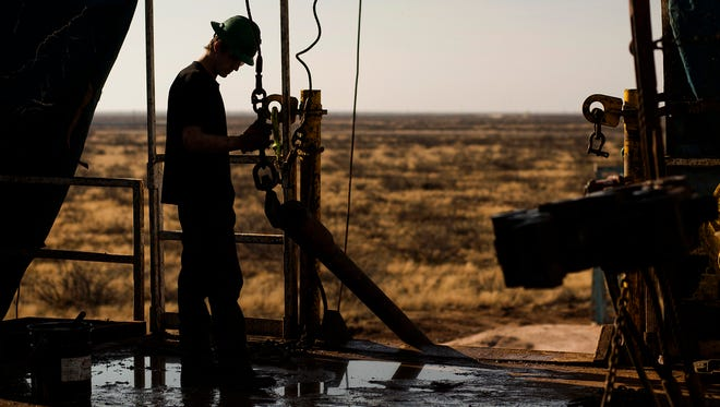 A worker waits to connect a drill bit on a Texas rig.  Despite improving oil prices, the industry remains in the doldrums..