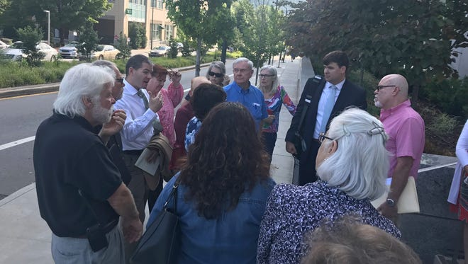 Attorney John D. Noor of Asheville-based Roberts & Stevens meets with East Asheville residents Tuesday outside the Buncombe County Courthouse. The residents, many of whom are part of the Eastmoor Homeowners Association, object to a proposed 214-unit housing development by South Carolina-based RAB Builders LLC.