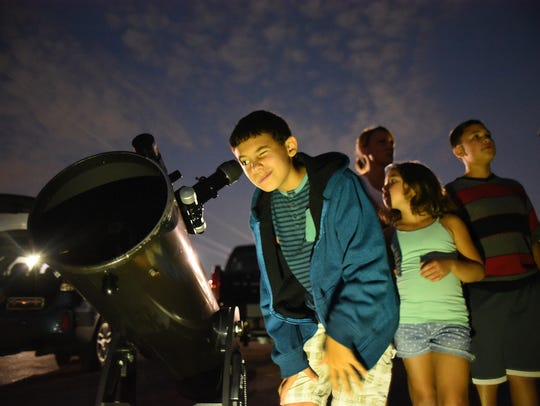 Ethan Durante looks at the planet Saturn during a stargazing