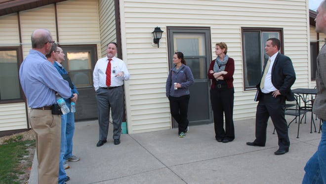 Members of the Marengo Memorial Hospital board listen as chief executive officer Barry Goettsch (center, in white shirt) talks about relocating staff to space in what was Kinsey Manor apartments, until March 1 when they were purchased by the hospital. They are standing outside a former apartment that will be used as the conference room. Graham Construction, the construction management firm for the hospital's renovation/building project, is using one apartment for its on-site office.