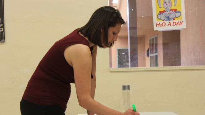 JMA administrative assistant Ashley Chavarria mark off students who have selected in the lottery draw on Thursday.
