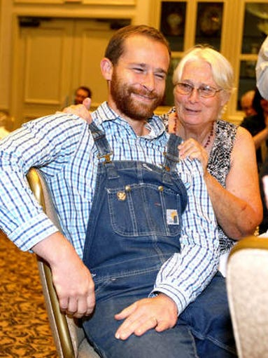 Nathan Ballentine gets a hug from his mother Sue Wiley after winning the Jefferson Award for Public Service during the Tallahassee Democrat's annual Volunteer of the Year awards at the University Center Club at FSU on Thursday afternoon.