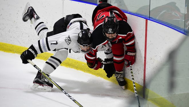 Tumbling into the boards Friday night are Plymouth's Graham Sheehan (7) and Livonia Churchill's Jordan Venegoni (12).