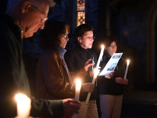 Eulalia Cabrera, second from right, of North Bergen reads a prayer written by the Rev. Dr. Laurie Ann Kraus of Presbyterian Disaster Assistance at Monday's vigil in response to the shooting in Las Vegas. Presbyterian Church in Leonia held the vigil on its front lawn.