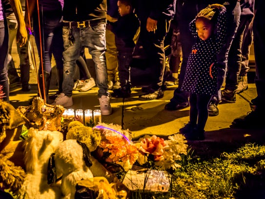 "Two-year-old Corynn Nelson looks down at a group of stuffed animals, candles and balloons left near the spot where Keshall ""KeKe"" Anderson was shot and killed in the 200 block of W. 20th Street in Wilmington at a vigil commemorating what would have been Anderson's 20th birthday."