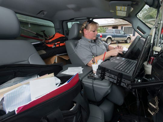 Escambia County Animal Control Officer Sgt. Stephanie Nowlin uses her county vehicle as an office to complete paper work between calls.