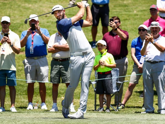 Golfer Dustin Johnson tees off during the InnerWorkings
