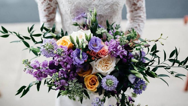 Lisianthus, scabiosa, fragrant garden roses, stock, Queen Anne's lace, vines and branches add to the lush, natural feel of JP Parker Flowers' American Garden-style bouquet.