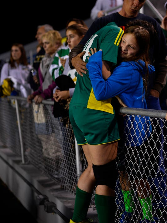 York Catholic's Tyler Baim, left, hugs her 9-year-old sister Brenna Baim and father Rob Baim after the Irish lost to Trinity in the District 3 Class A girls' soccer championship game in Hershey.