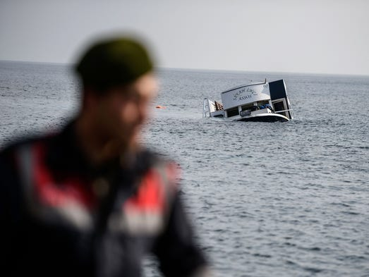 A sinking boat is seen behind a Turkish gendarme off