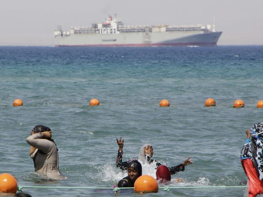FILE - In this Sunday, Aug. 9, 2015 file photo, a ship crosses the Gulf of Suez towards the Red Sea as holiday-makers swim in Suez, 127 kilometers (79 miles) east of Cairo, Egypt.