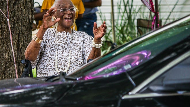 Katherine Scott greets passersby during her 100th birthday drive-by celebration at her home in Athens, Ga., on Saturday, Sept. 5, 2020.
