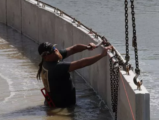 Bubba Williamson works to install a new seawall at