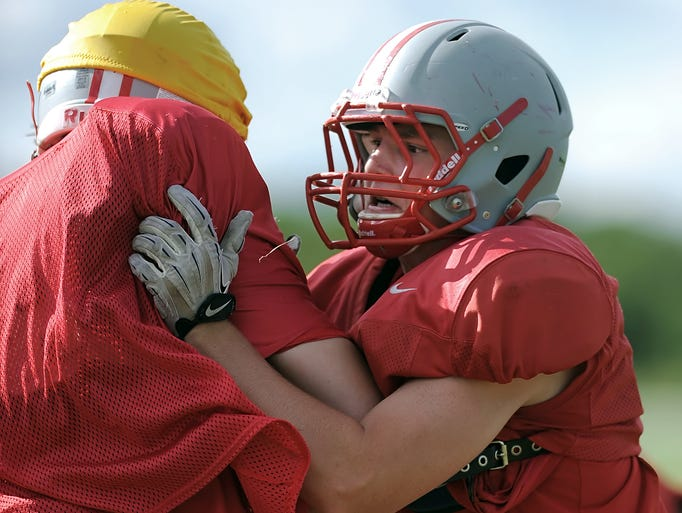 Canandaigua's Ryan Heeb, right, looks for the ball carrier trying to shake a block during preseason football practice at Canandaigua Academy on Thursday, August 28, 2014.
