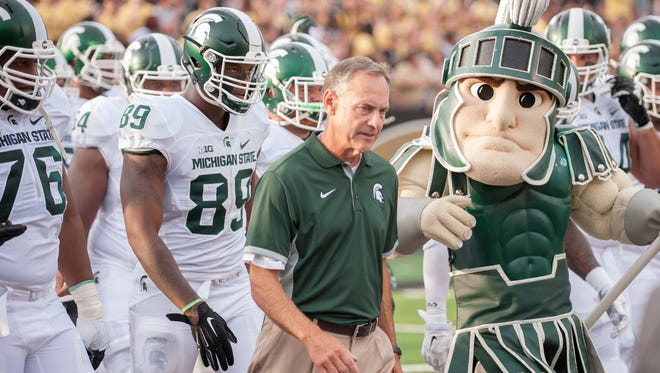 Spartans head coach Mark Dantonio takes the field with Sparty and the Michigan State Spartans Friday night.