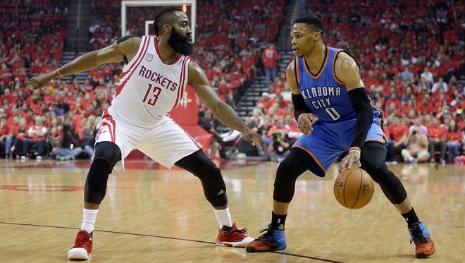 Oklahoma City Thunder guard Russell Westbrook dribbles against Houston Rockets guard James Harden in the first quarter in Game 5 of the first round of the 2017 NBA Playoffs.