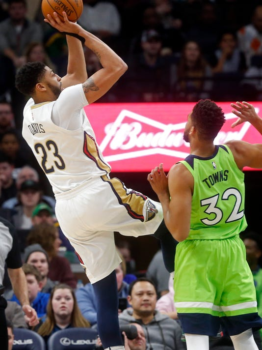 New Orleans Pelicans' Anthony Davis, left, shoots as Minnesota Timberwolves' Karl-Anthony Towns looks on in the first half of an NBA basketball game Saturday, Feb. 3, 2018, in Minneapolis. (AP Photo/Jim Mone)