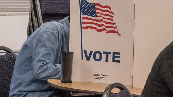 A voter fills out his ballot at Maple United Methodist Church on Tuesday.