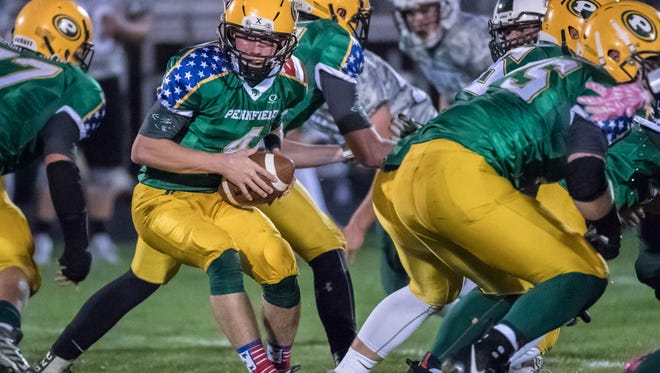 Pennfield's Jack Day hands off the ball during first half action against Olivet Friday evening.