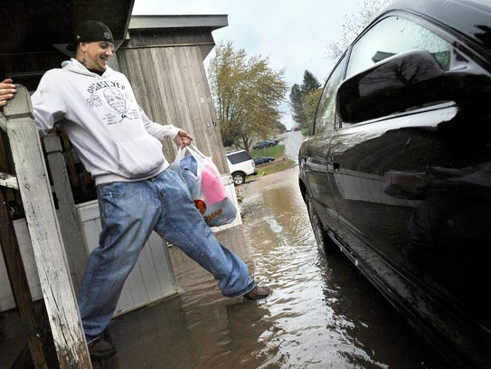 Kevin Critser steps into a flooded roadway in front