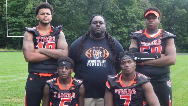 Spring Valley senior Tyreke Smith (pictured bottom left) and fellow captains Devan Lawson (10), Josh Ramponeau (50) and Ori Jean-Charles, along with head coach Andrew Delva.