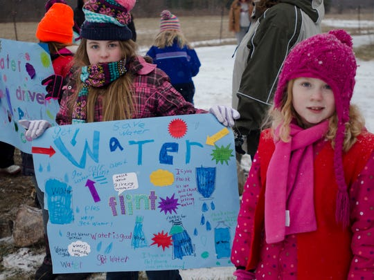 Members from the Frontier Girls of Avoca show homemade signs supporting their water bottle drive for Flint residents who are in the midst of a water contamination crisis.