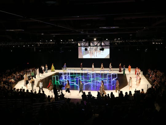 Models surround the runway at the conclusion of Friday's