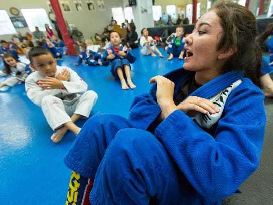 Jaylynn Benitez, 16, leads a warmup during  a class