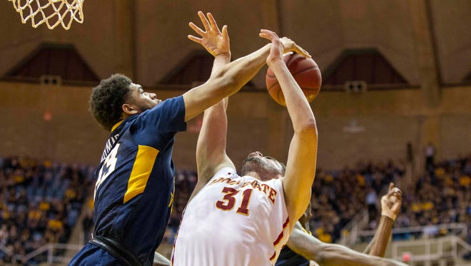 Iowa State forward Georges Niang (31) is blocked by West Virginia  forward Esa Ahmad (23) during the first half at the WVU Coliseum.