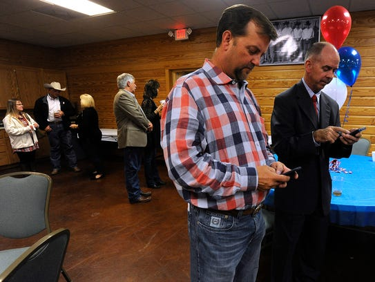 Jay Evans (center), president of the Taylor County Expo Center board, and Kelly Gill, past president of the expo center, check election results on their phones during an election watch party in 2016.