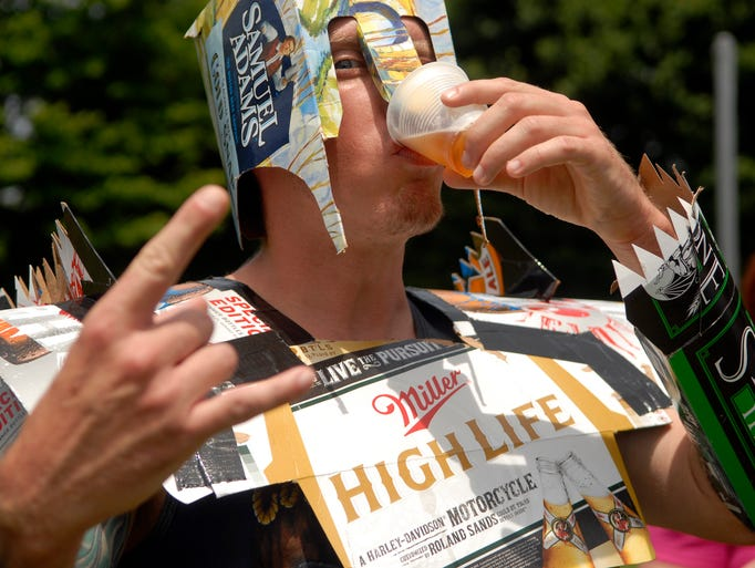 Josh Lesch chugs his beer at the first stop on the 4K Tap N Run at E.P. Tom Sawyer Park.  The Tap N Run features stations along the course where runners must drink 5oz. of beer before they continue with their run.  June 14, 2014