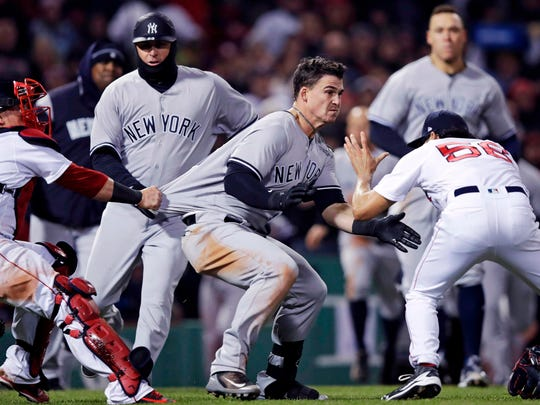 New York Yankees' Tyler Austin, center, rushes Boston Red Sox relief pitcher Joe Kelly, right, after being hit by a pitch during the seventh inning of a baseball game at Fenway Park in Boston, Wednesday, April 11, 2018. At left holding back Austin is Red Sox catcher Christian Vazquez.