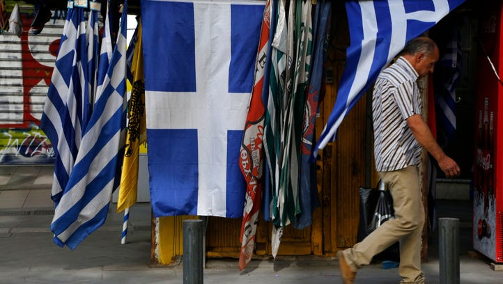 A man passes a kiosk selling Greek flags in central