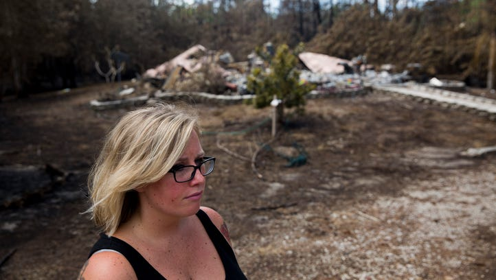 Lindsey Rotondo stands outside the remains of her home