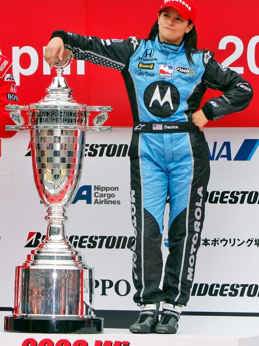 FILE - In this April 20, 2008, file photo, American Danica Patrick, of Andretti Green Racing, poses alongside the trophy on the podium after winning the IndyCar auto race at Twin Ring Motegi in Motegi, Japan. Patrick will race only 2 more times next season and end her career at the Indianapolis 500. It will end nearly 2 decades of racing for one of the most recognizable athletes in the world and send Patrick to a new phase of her life. (AP Photo/Shuji Kajiyama, File)