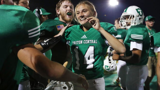 Triton Central kicker Samantha Dewey celebrates with the team, including Griffin Reid, to her left, after her 35-point extra point late in the game as the Tigers tied Lutheran High School 14-14 on Friday, September 5, 2014. Minutes later, Dewey kicked a 23-yard field goal to win the game 17-14 on their home field in Fairland.